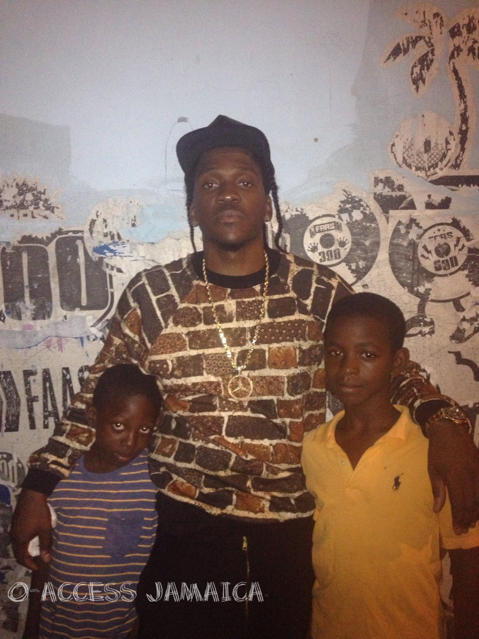 Pusha T hangs out with some kids in downtown Kingston.