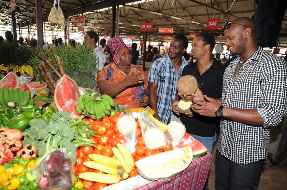 Photo By Lowrie-Chin Nesta Carter, Michael Frater and Asafa Powell show Gold Medal support for the Eat Jamaican Campaign as they commend Coronation Market vendor Angela Jarrett.